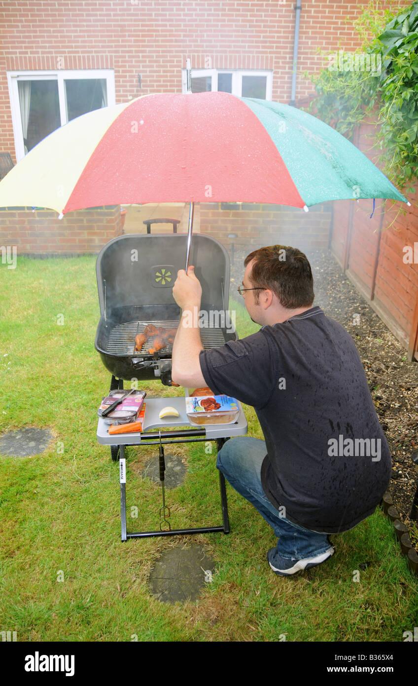 L Uomo Avente Un Barbecue Nel Suo Giardino Sotto La Pioggia Regno