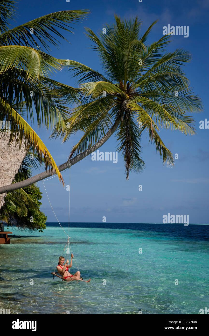 Ragazza basculante in swing corda sull'Atollo di Ari Sud alle Maldive nei pressi di India Immagini Stock