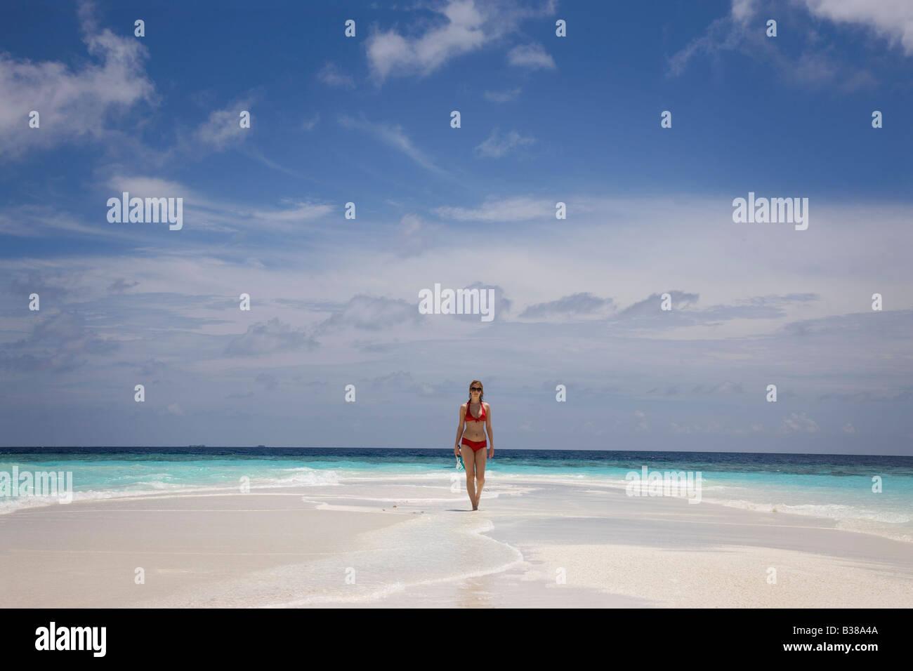 Giovane Donna che cammina lungo i deserti di spiaggia di sabbia bianca circondata da acque tropicali delle Maldive Foto Stock
