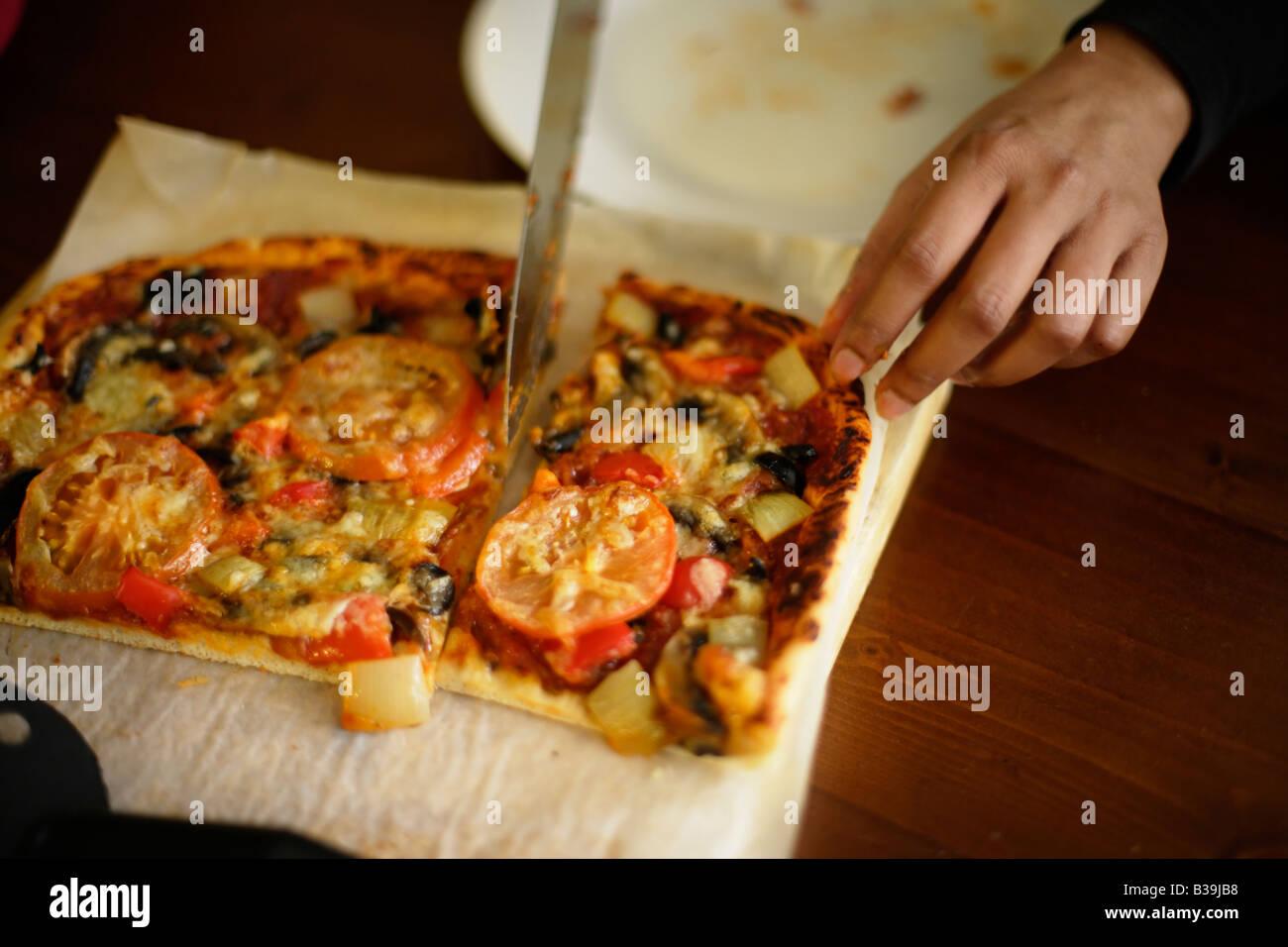 Pizze donna Indiana che taglia una fetta Immagini Stock