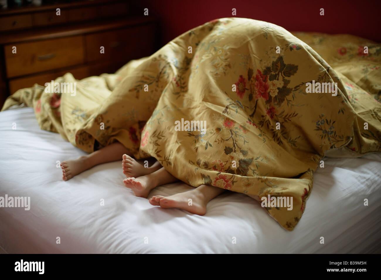 Fratello e Sorella sotto i coperchi del genitore s bed ragazza di età compresa tra i 5 e ragazzo 6 Immagini Stock
