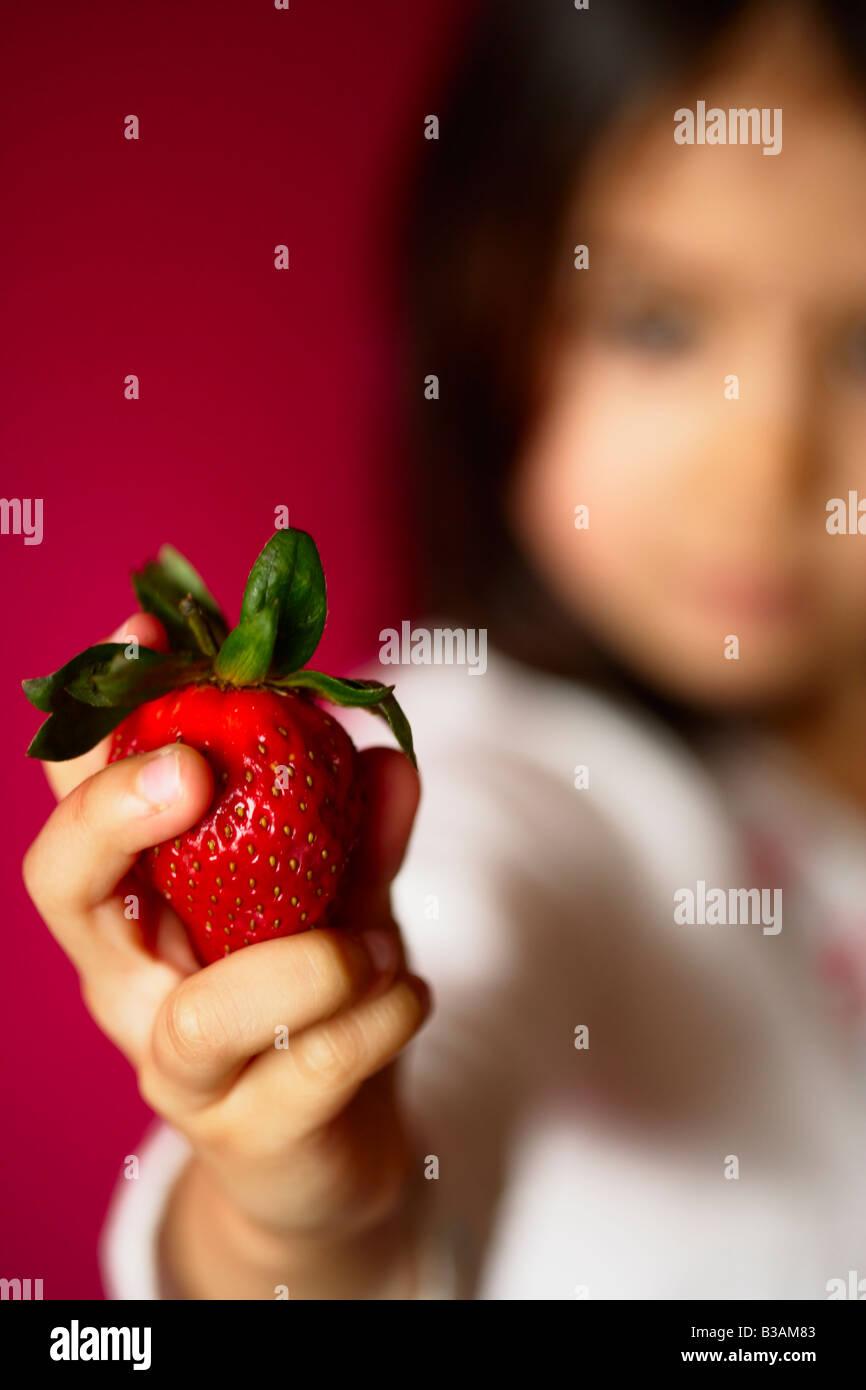 Bambina di cinque anni detiene fragola Immagini Stock