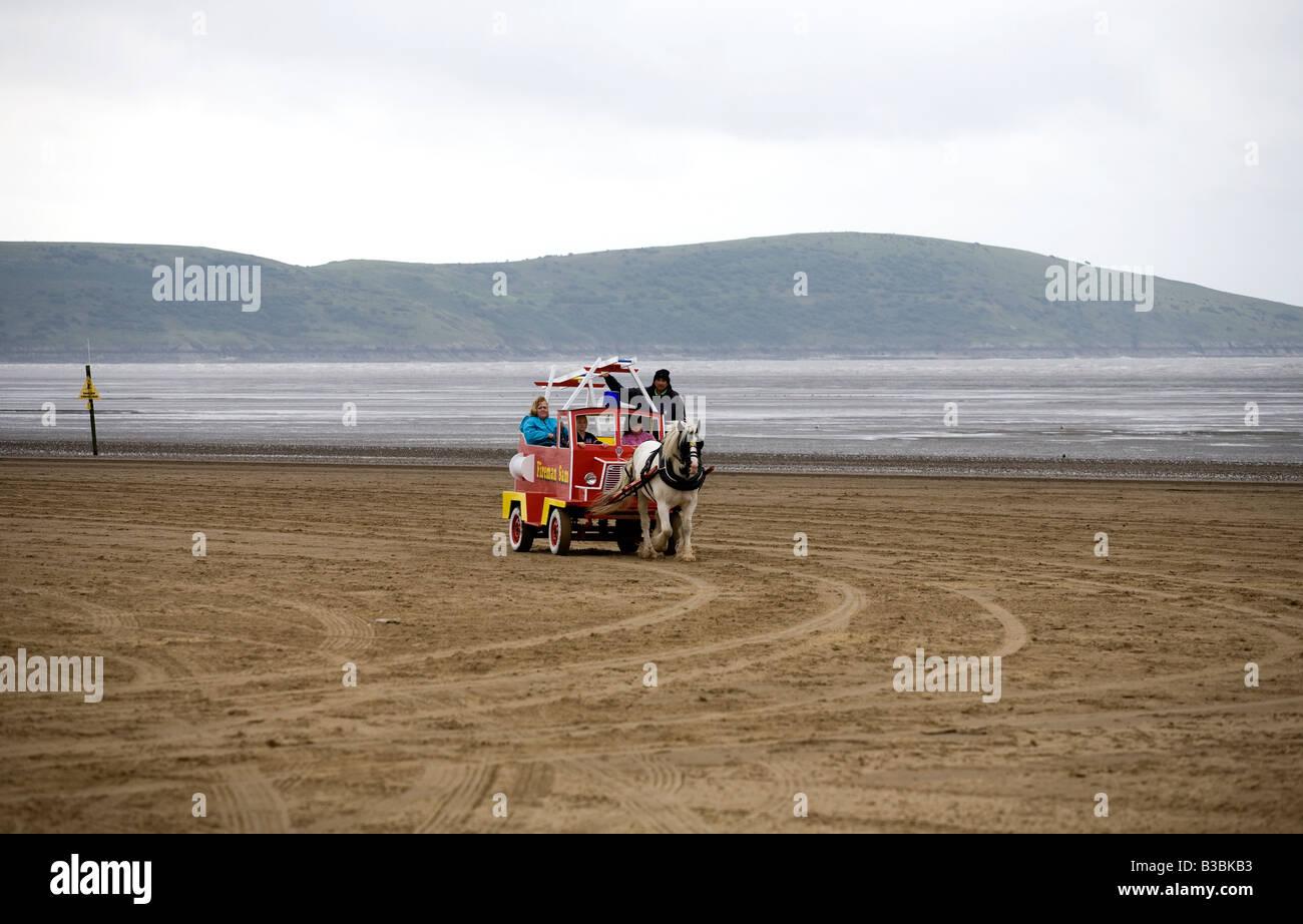 Un cavallo giocattolo motore fire sulla sabbia a Weston Super Mare sul grigio di un giorno di estate in agosto Immagini Stock