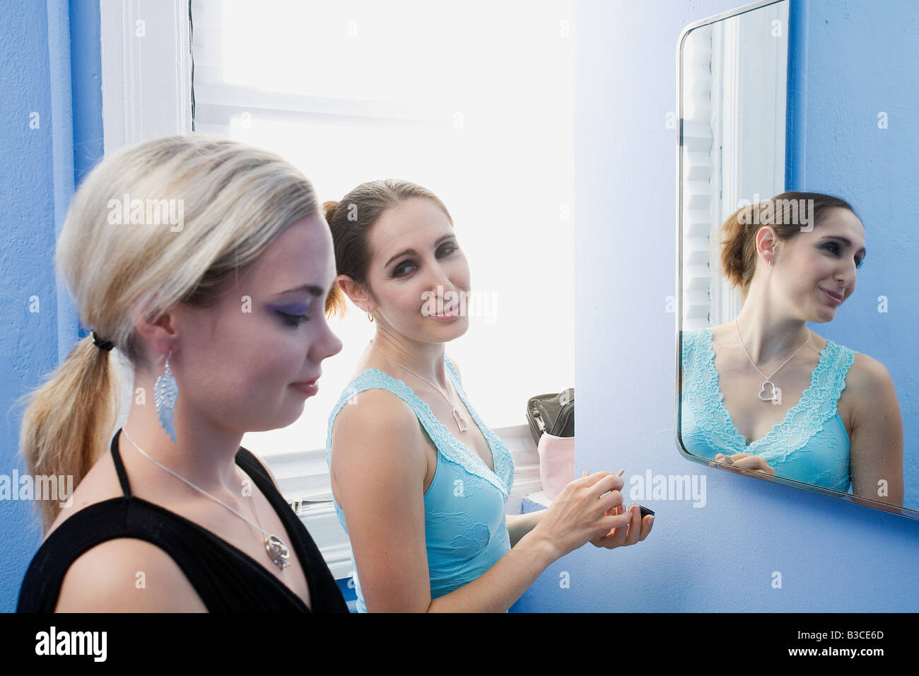 Giovani donne in piedi nella parte anteriore dello specchio Immagini Stock