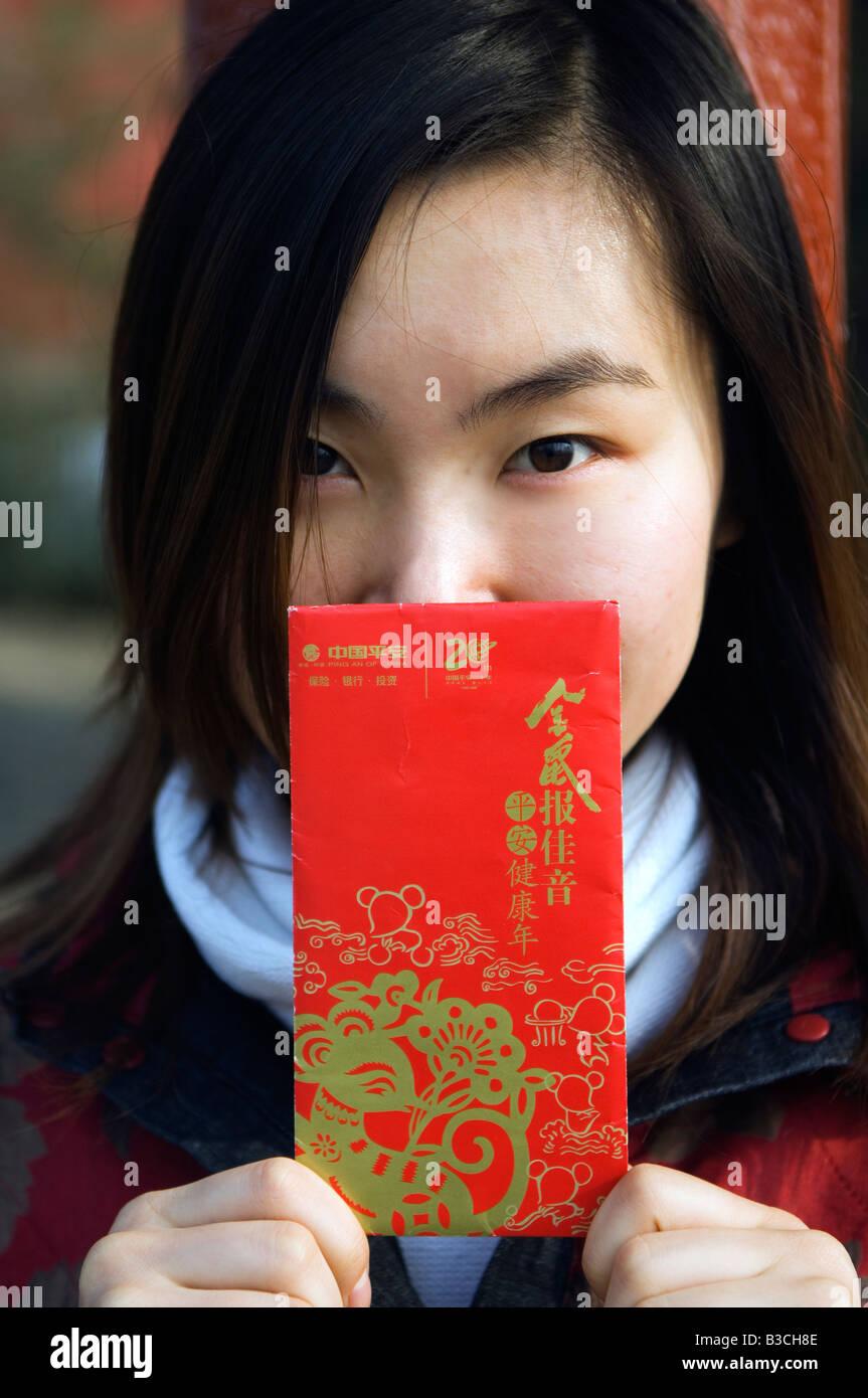 Cina, Pechino. Una ragazza cinese indossando il tradizionale stile Cinese vestiti tenendo un Hongbao busta che viene Foto Stock