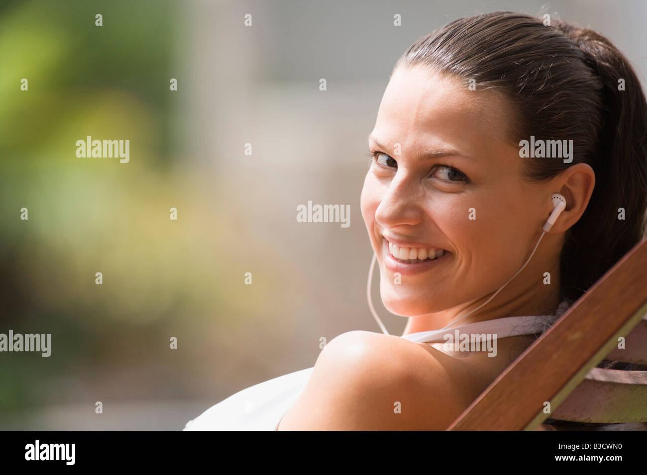 Giovane donna in sedia a sdraio ascoltando mp3-Player, ritratto Immagini Stock
