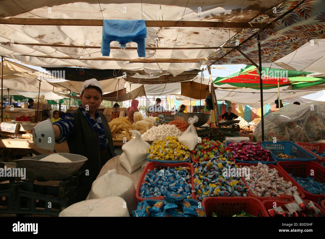 Venditore a vendere zucchero e bon ossa presso il mercato centrale in Urgench, Uzbekistan Immagini Stock