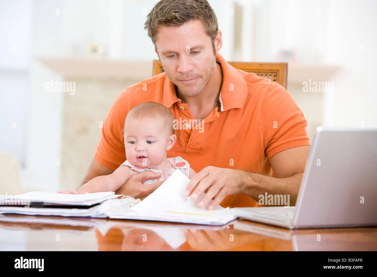Il padre e il bambino nella sala da pranzo con il computer portatile Foto Stock