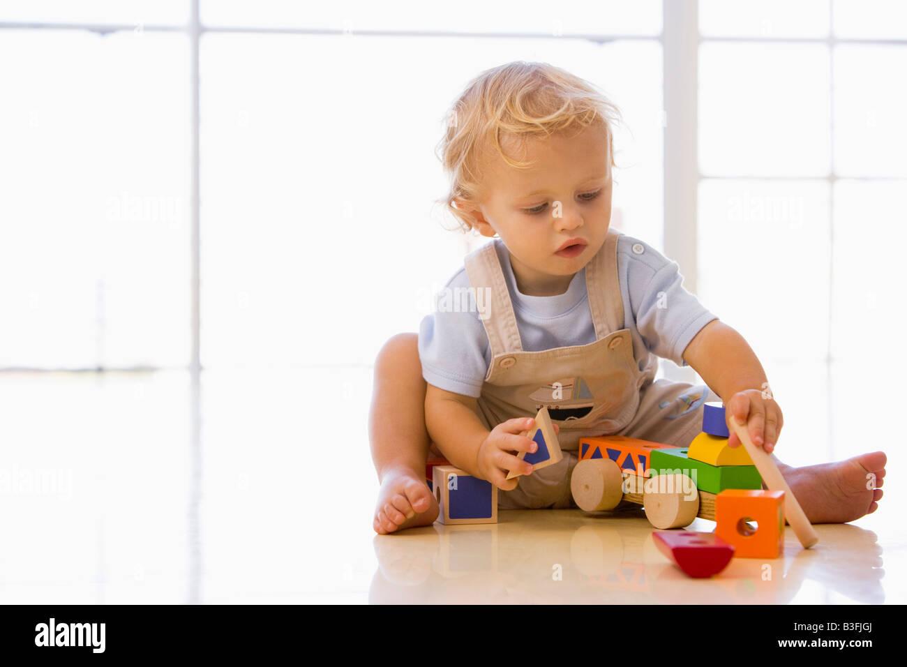 Baby indoor giocando con il giocattolo carrello Immagini Stock