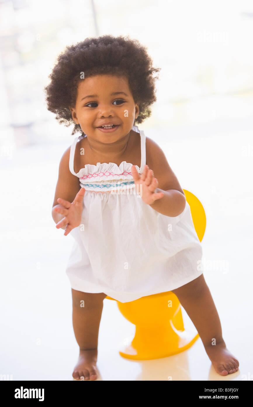 Baby in interni di andare sul vasino sorridente Immagini Stock