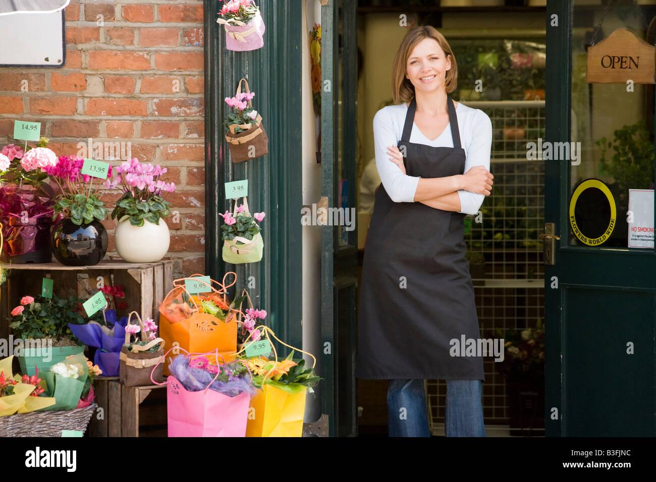 La donna lavora al negozio di fiori sorridenti Immagini Stock