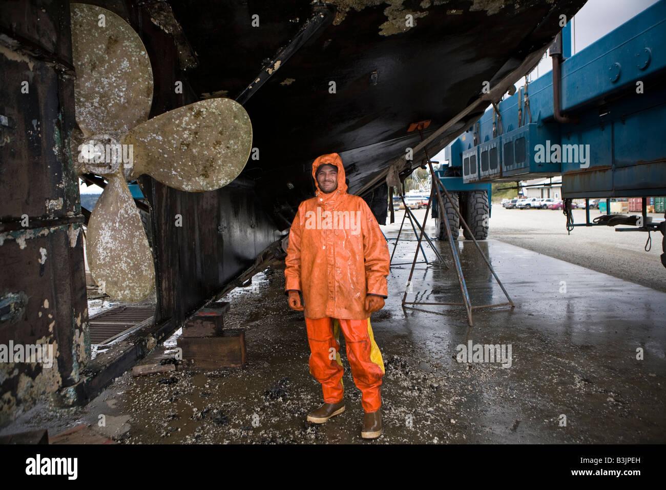 Robert Palmer lavaggi a pressione la parte inferiore di un 88 piedi lungo la pesca in barca Leann nel cantiere navale di Port Townsend Foto Stock