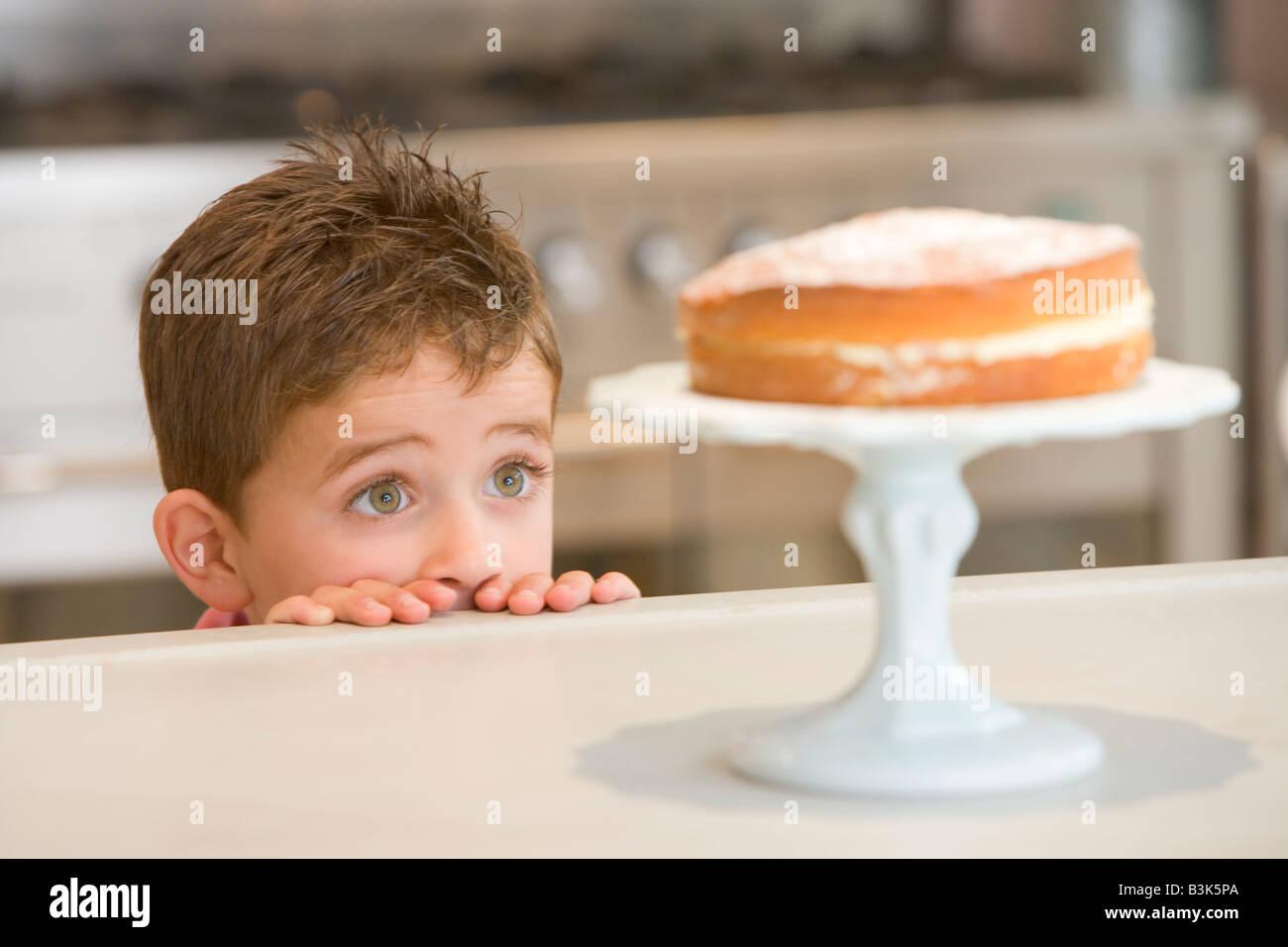 Giovane ragazzo in cucina guardando la torta sul contatore Immagini Stock