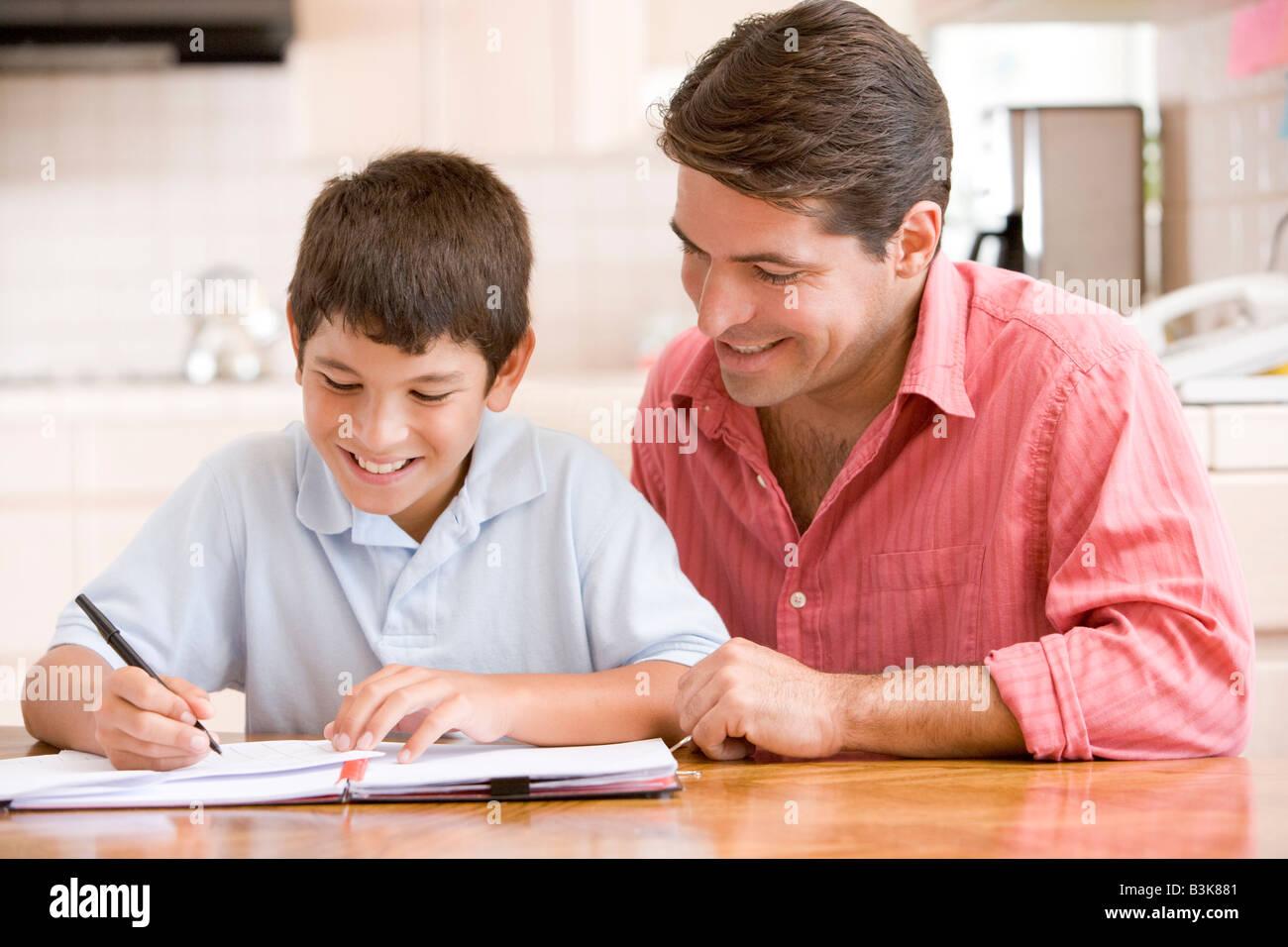 L'uomo aiutando giovane ragazzo in cucina a fare i compiti di scuola e sorridente Immagini Stock