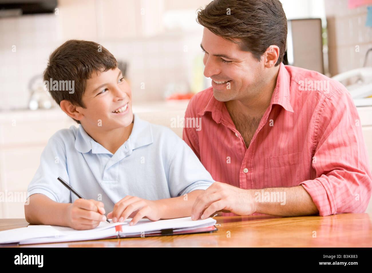 L'uomo aiutando giovane ragazzo in cucina a fare i compiti di scuola e sorridente Foto Stock
