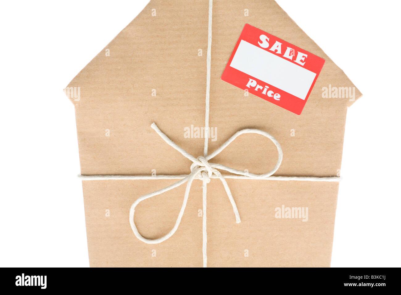 Studio shot di casa avvolta in carta marrone con adesivo di vendita Immagini Stock