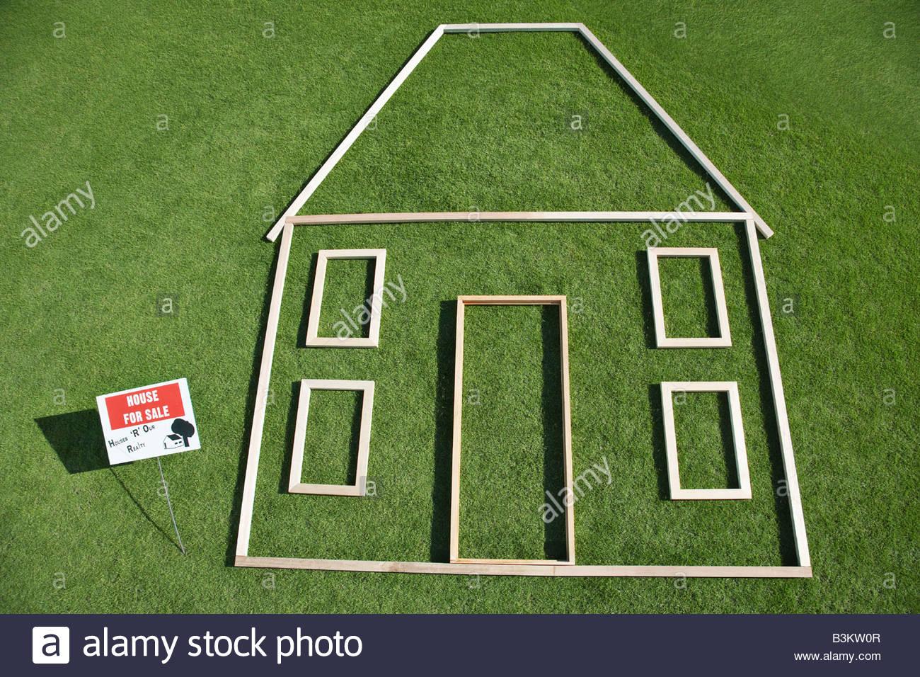 """""""In vendita"""" segno e casa contorno in erba Immagini Stock"""