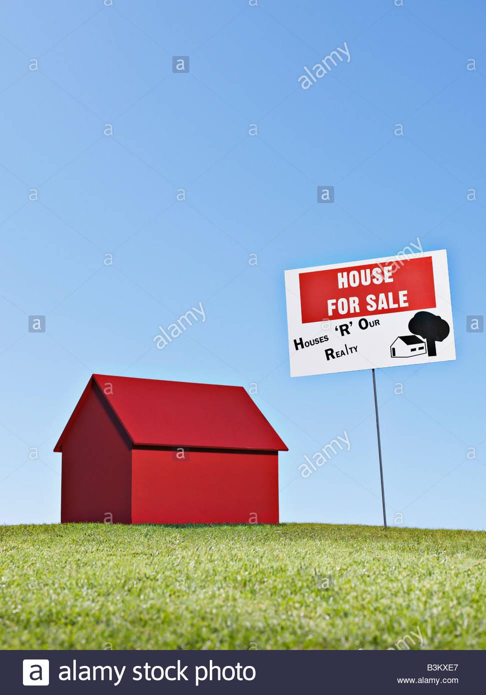 """Modello di piccola casa accanto a """"in vendita"""" segno Immagini Stock"""