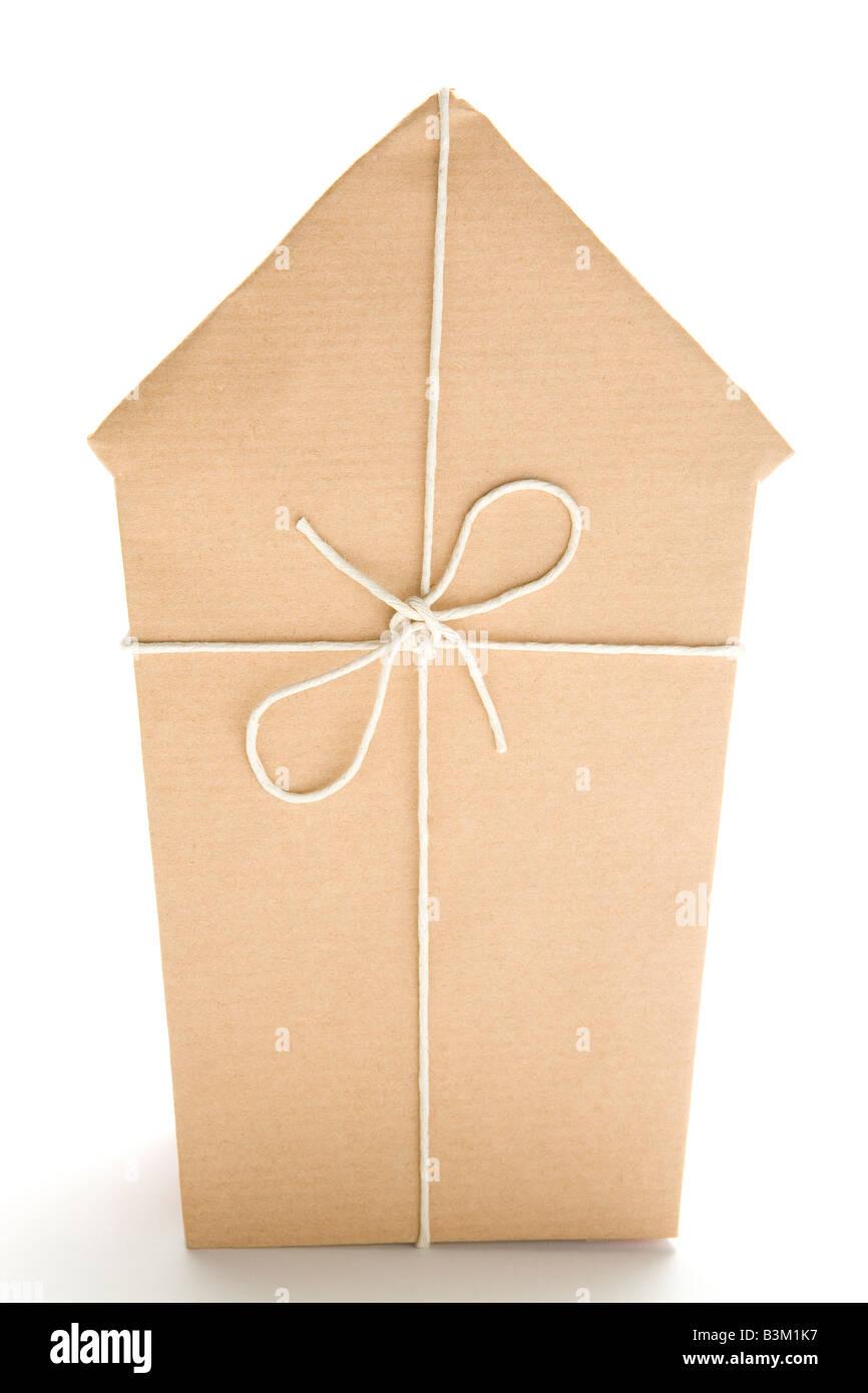 Studio shot di casa avvolta in carta marrone e legati con spago Immagini Stock