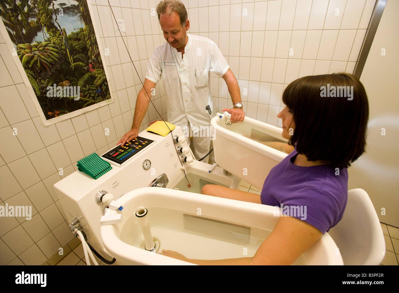 Massaggiatore supervisiona la somministrazione di un elettro-bagno ...