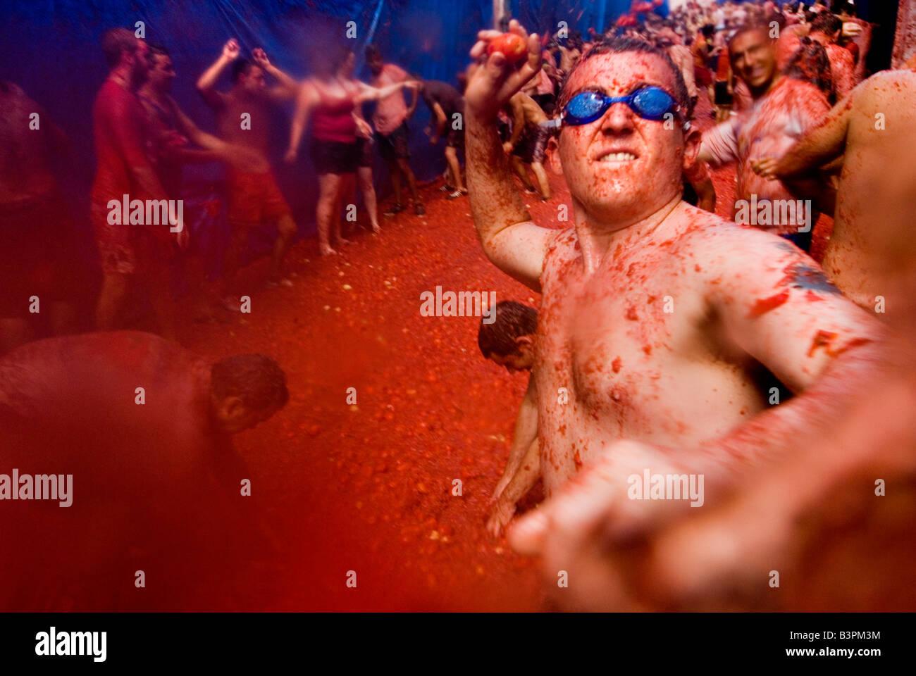 Uomo che indossa gli occhiali per nuoto gettando un pomodoro a La Tomatina food festival di combattimento. Bunol. Immagini Stock