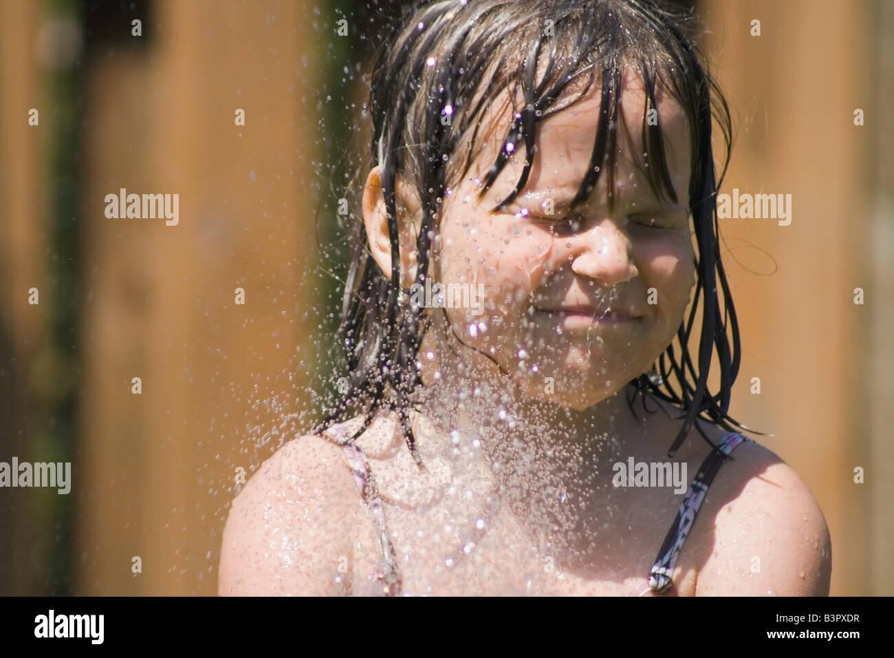 Ragazza giovane getting spruzzato in faccia con un tubo flessibile da giardino Immagini Stock