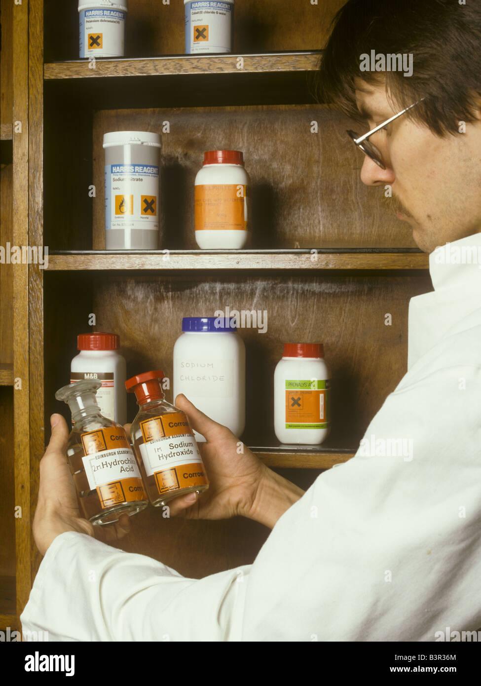 Tecnico di laboratorio può contenere bottiglie reagenti di prodotti chimici corrosivi Immagini Stock