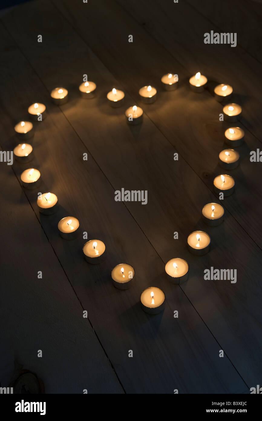 Candele illuminate collocato in una forma di cuore Immagini Stock