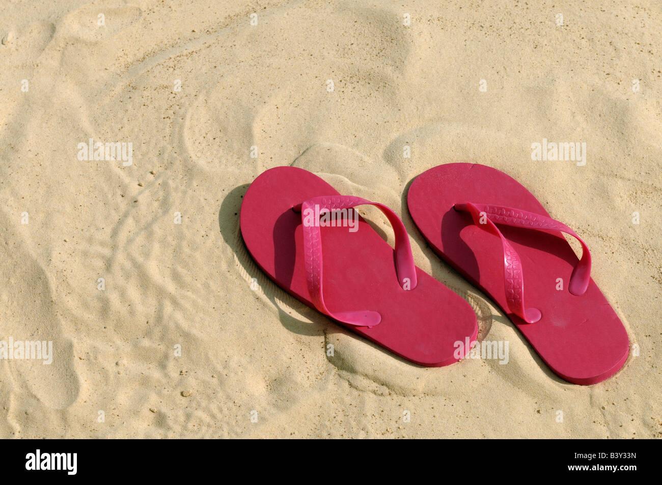 Rosa flip flop su una spiaggia Foto Stock