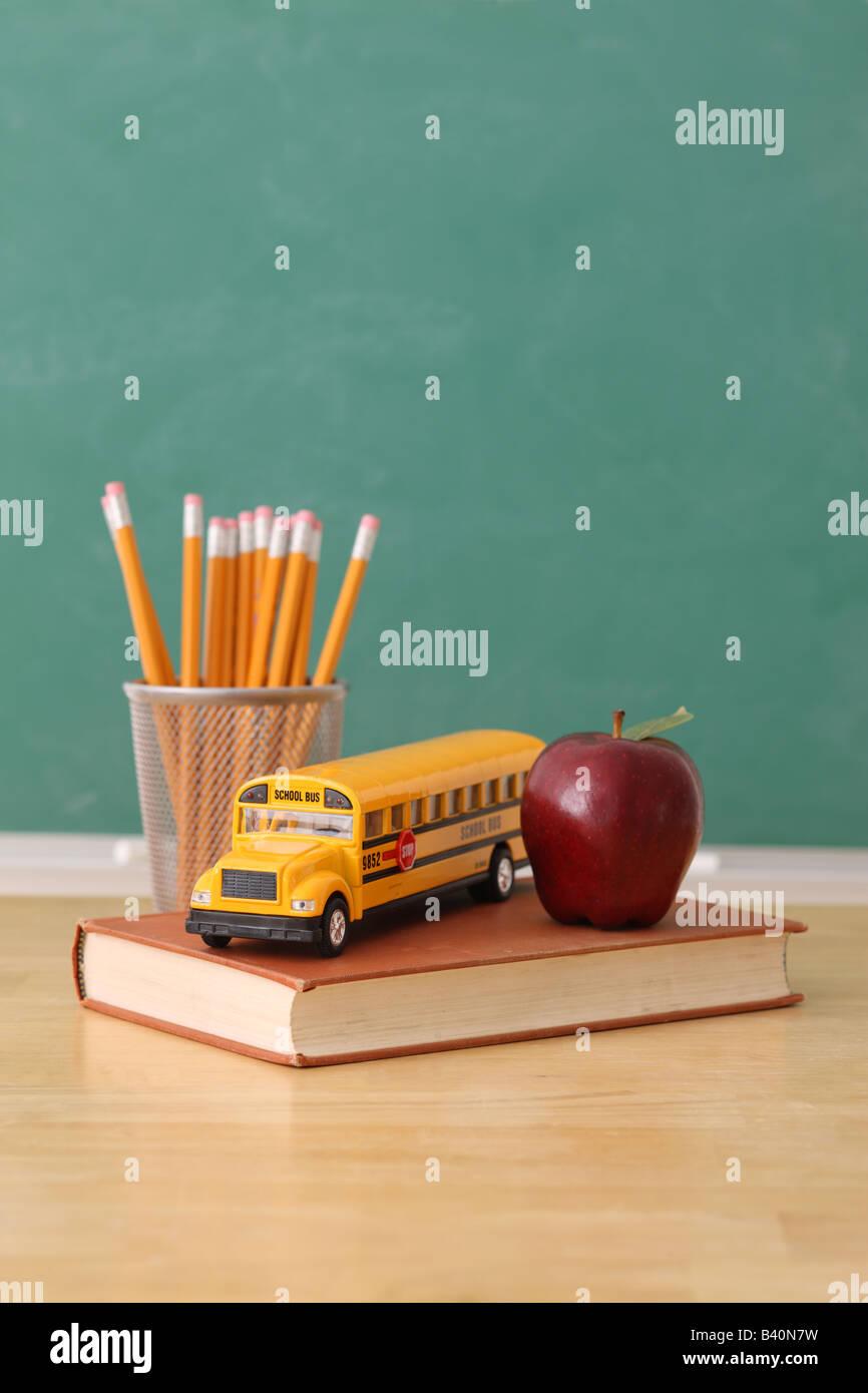 Istruzione scolastica ancora vita con matite apple libro giocattolo e scuola bus sfondo lavagna Immagini Stock