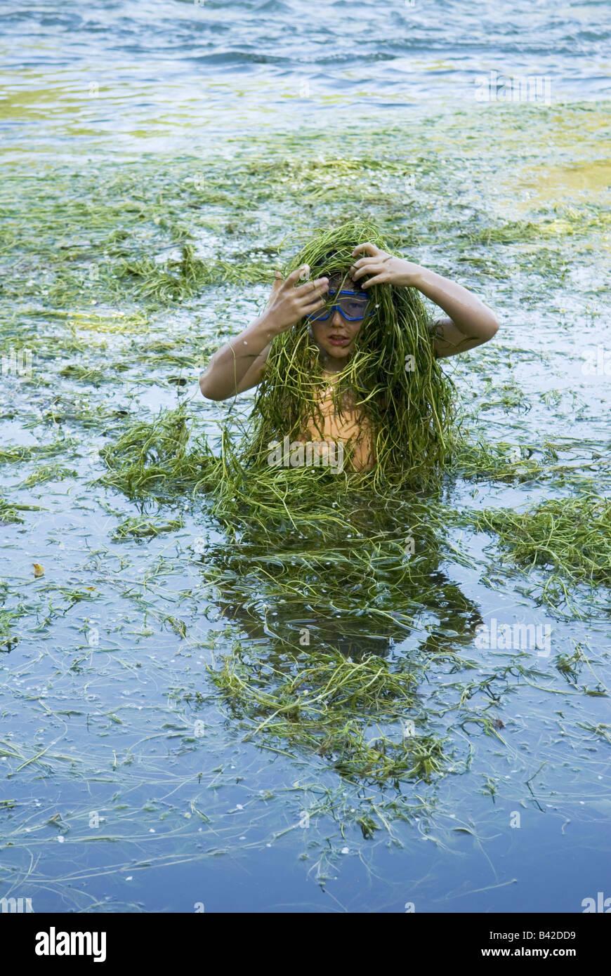 Un giovane ragazzo fino alla sua vita nel fiume copre se stesso in weed durante un gioco Immagini Stock