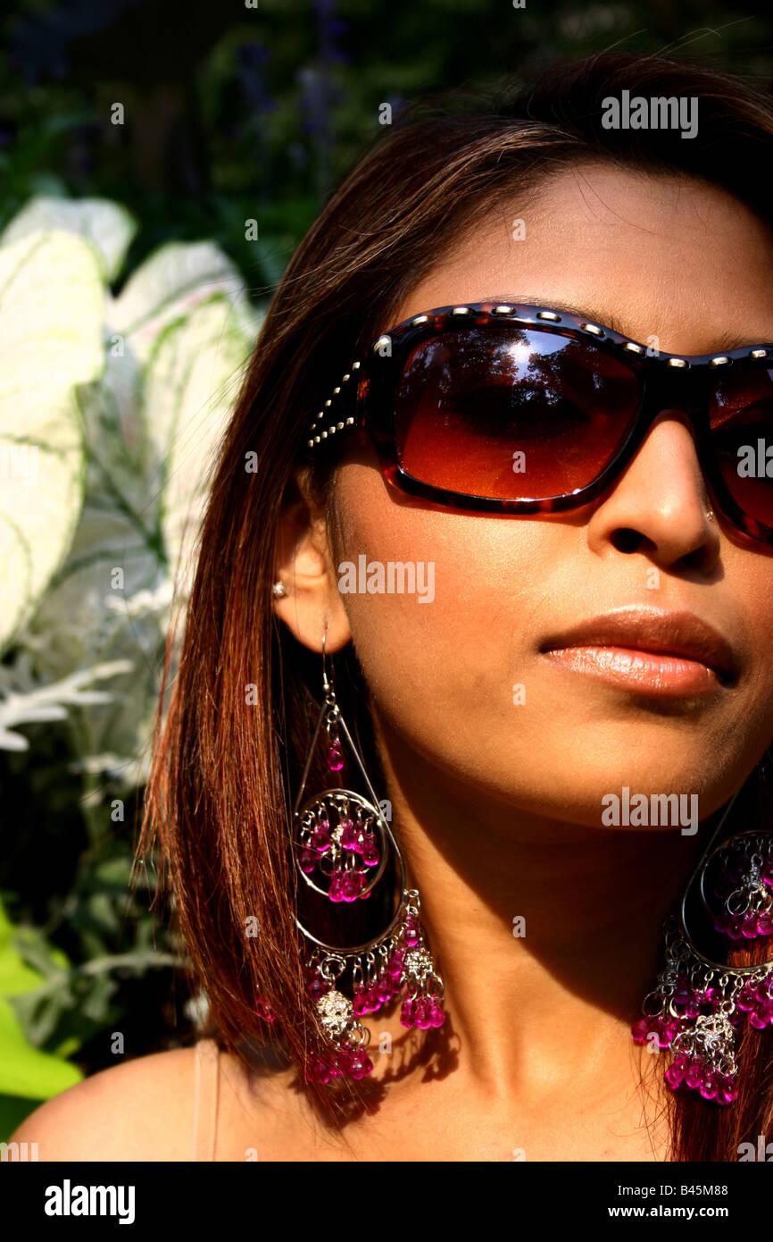 Ritratto di una donna che indossa alla moda, elegante occhiali da sole. Foto Stock