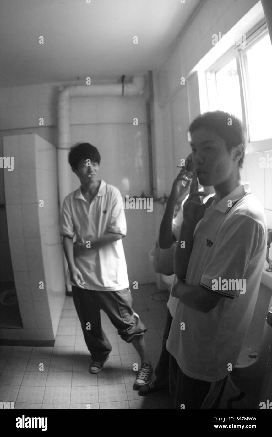 Giovani ragazzi cinesi di fumare nei ragazzi restroom durante pausa di  classe Immagini Stock 1d404edfb48b