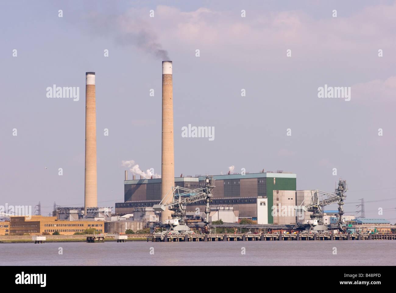 Fumo nero emesso da uno di una coppia di camini di Barking Coal Fired power station sulle rive del fiume Tamigi Immagini Stock