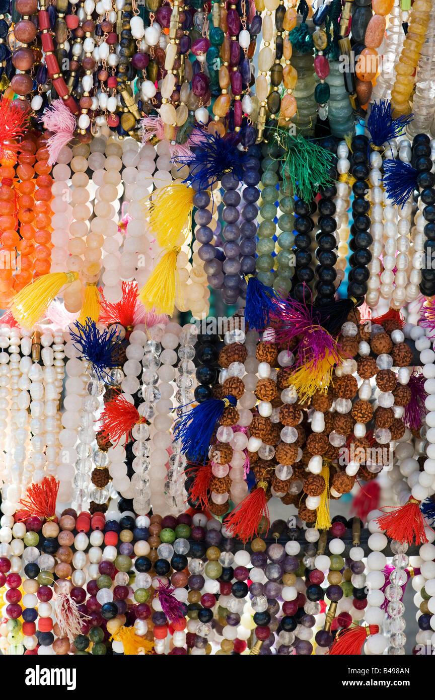 Polso japamalas religiosi o conteggio delle perle pendenti da un mercato in stallo in India Foto Stock