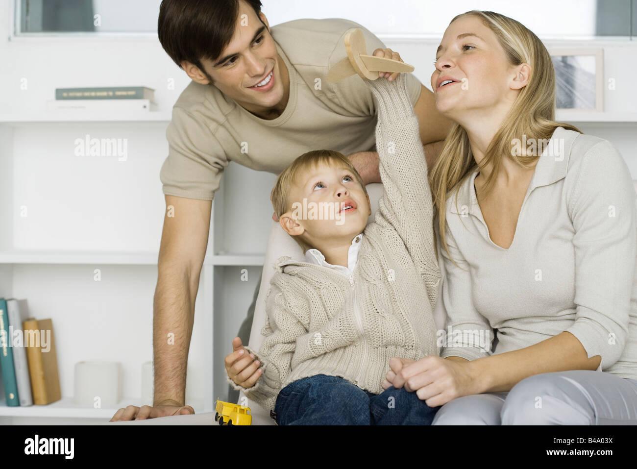 Little Boy giocando con aeroplano giocattolo, i genitori a guardare Foto Stock