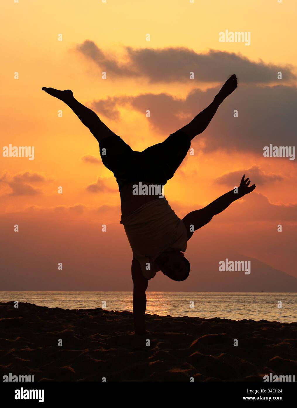 Giovane uomo sta facendo un incredibile handstand al tramonto Immagini Stock