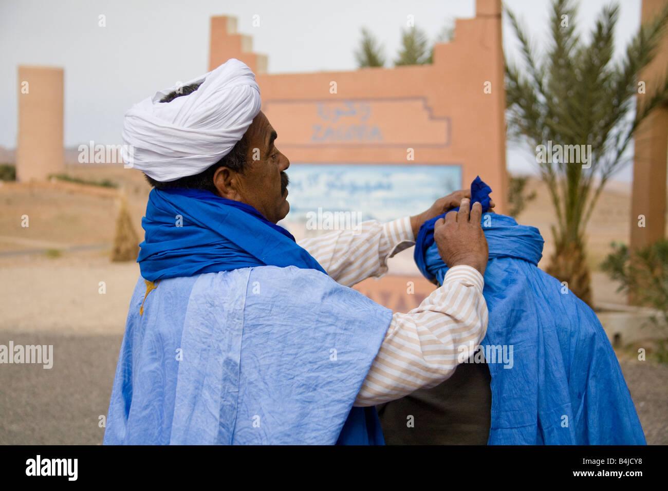 Merchant trader mettendo sul coperchio di testa turbante sulla testa turistica Zagora Marocco.orizzontale.89919 Immagini Stock