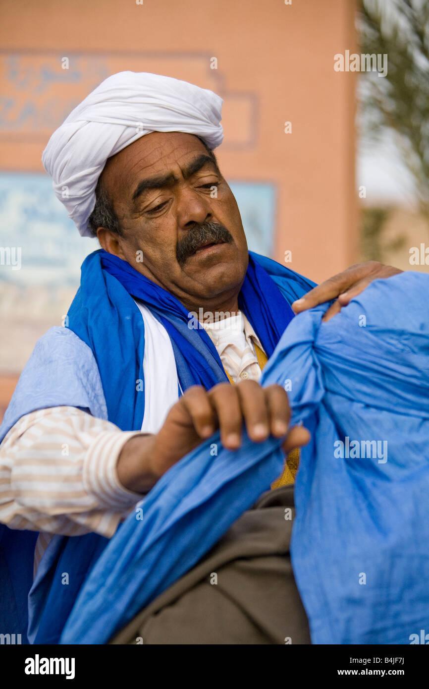 Merchant trader mettendo sul coperchio di testa turbante sulla testa turistica Zagora Marocco.verticalal.89918_Marocco Immagini Stock