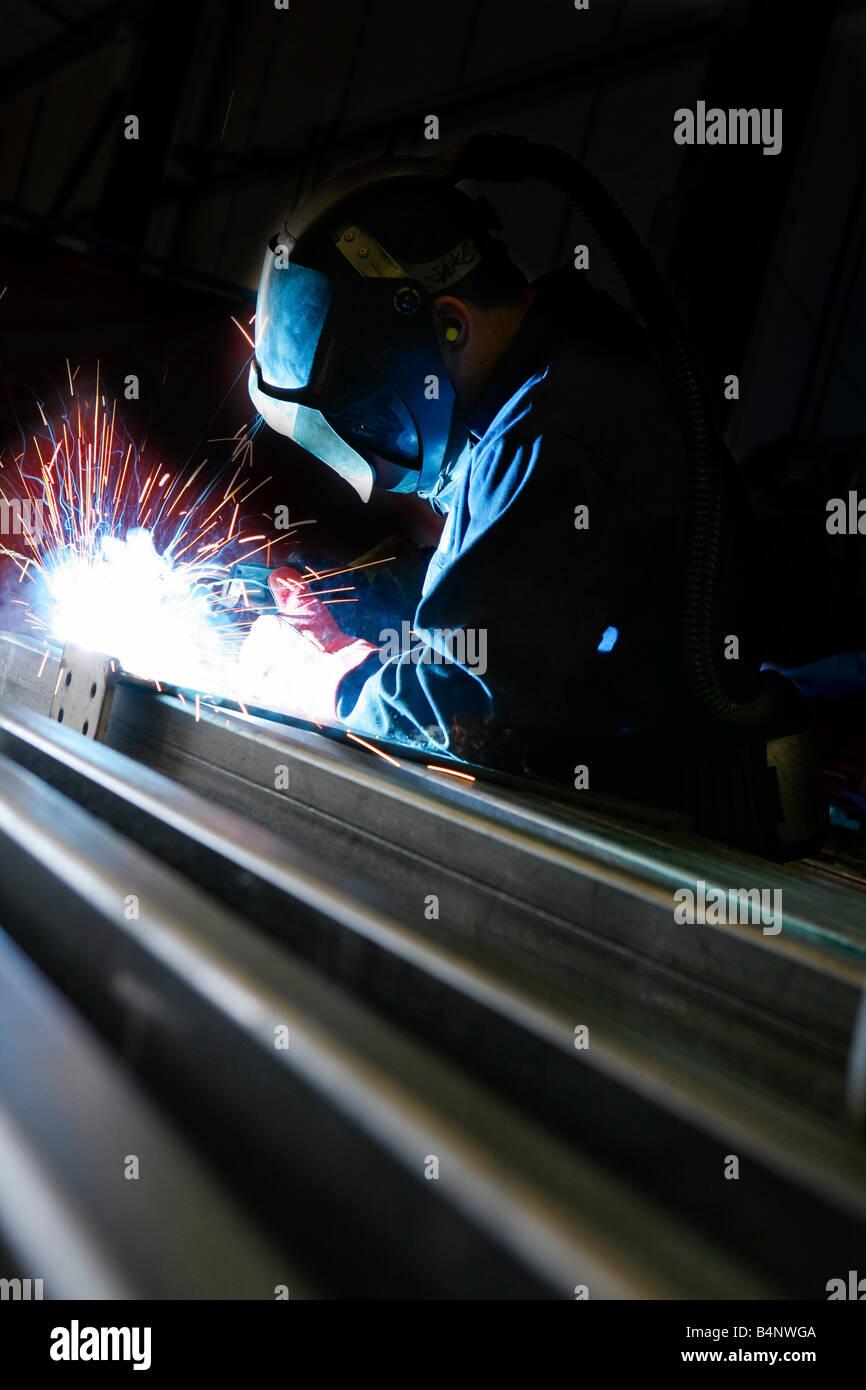 Saldatura ad arco sul metallo in ambiente industriale Immagini Stock
