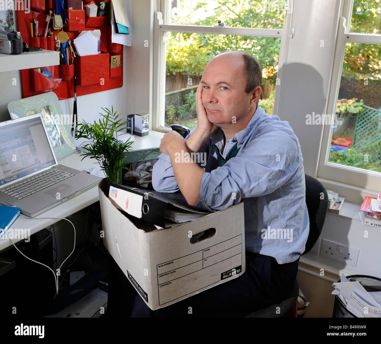 Triste e preoccupato uomo pacchi fino la sua scrivania e beni dopo aver perso il suo lavoro, essendo reso ridondante, Immagini Stock