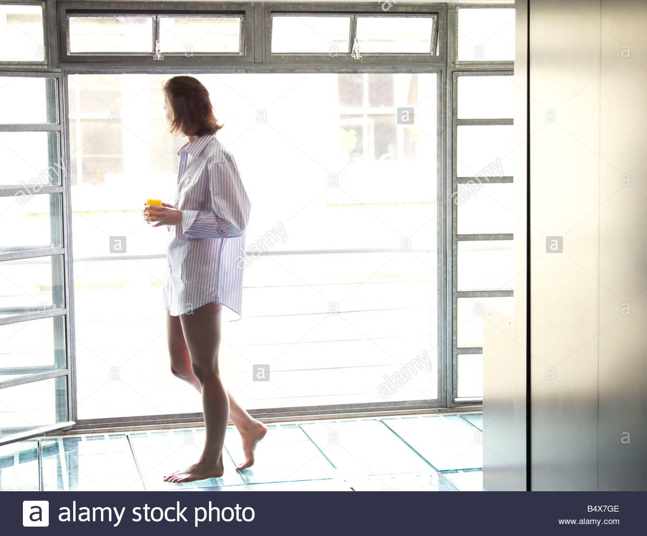 Donna che cammina nella finestra del passato in mattinata Immagini Stock