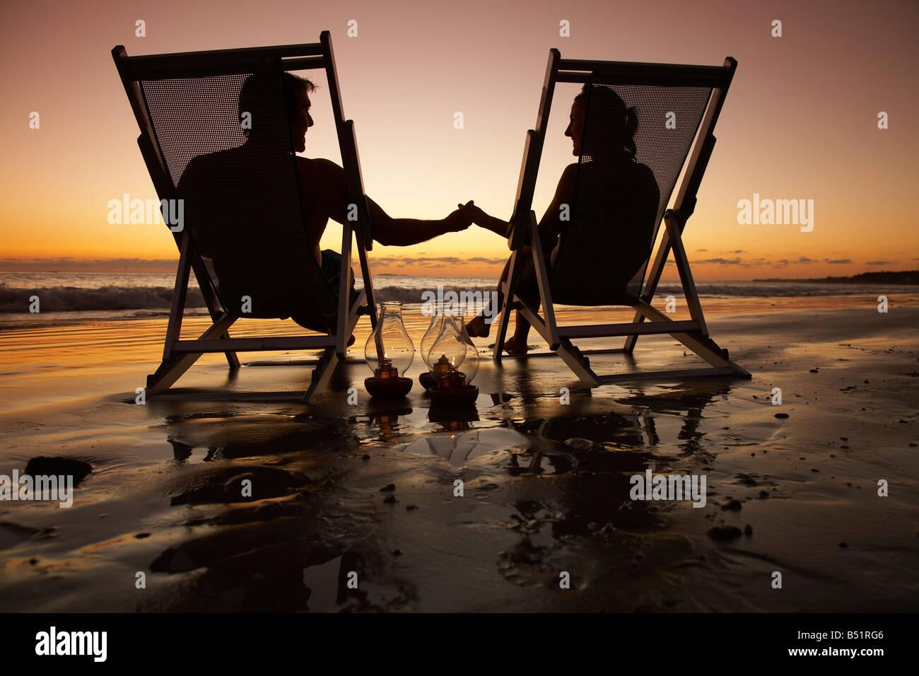 Giovane seduto in sedie a sdraio sulla spiaggia al tramonto, Messico Foto Stock