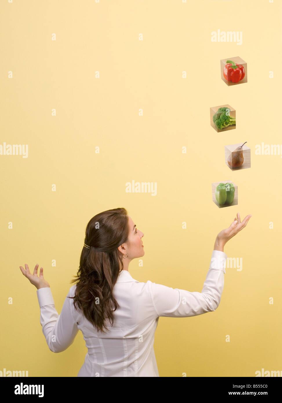 Donna di lanci blocchi alimentari nell'aria nutrizione salute Dieta mangiare Immagini Stock
