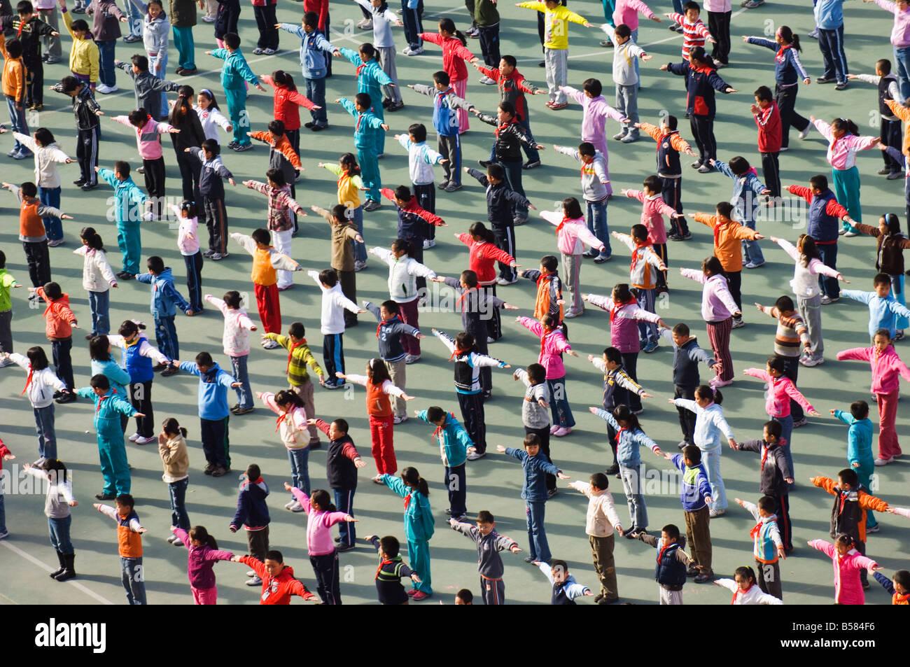 Junior scuola bambini esercitando in abiti colorati, Pechino, Cina e Asia Immagini Stock