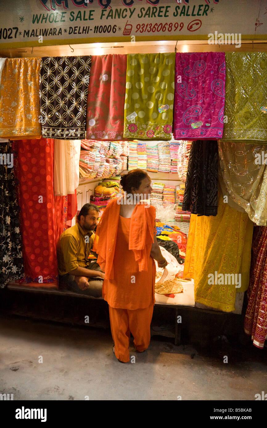 Una donna di saris di acquisto in un negozio nel mercato Kinari, 'Old Delhi' India Foto Stock