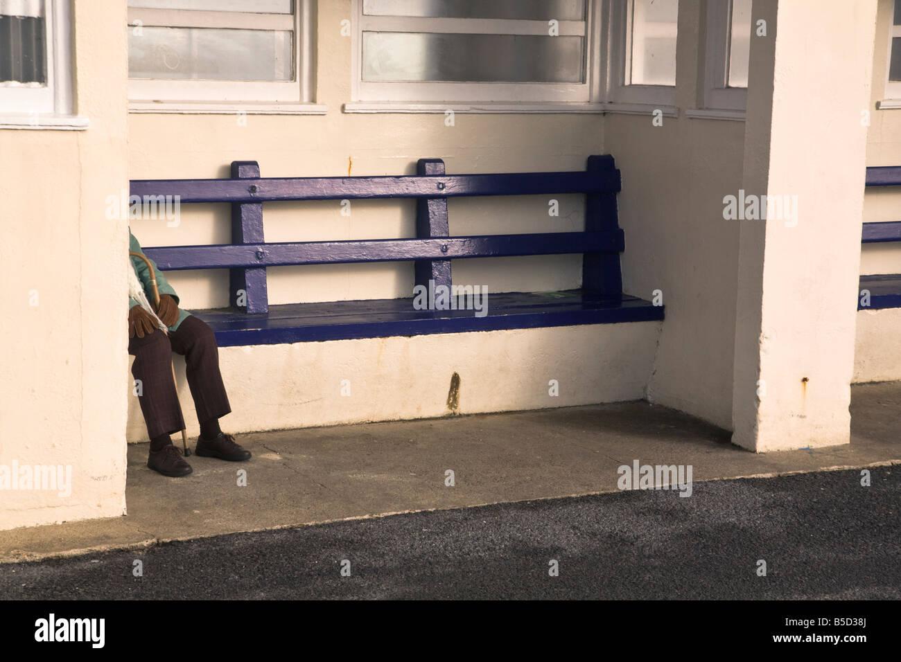 Panchina Lungomare : Vista offuscata della donna anziana seduta su una panchina sul