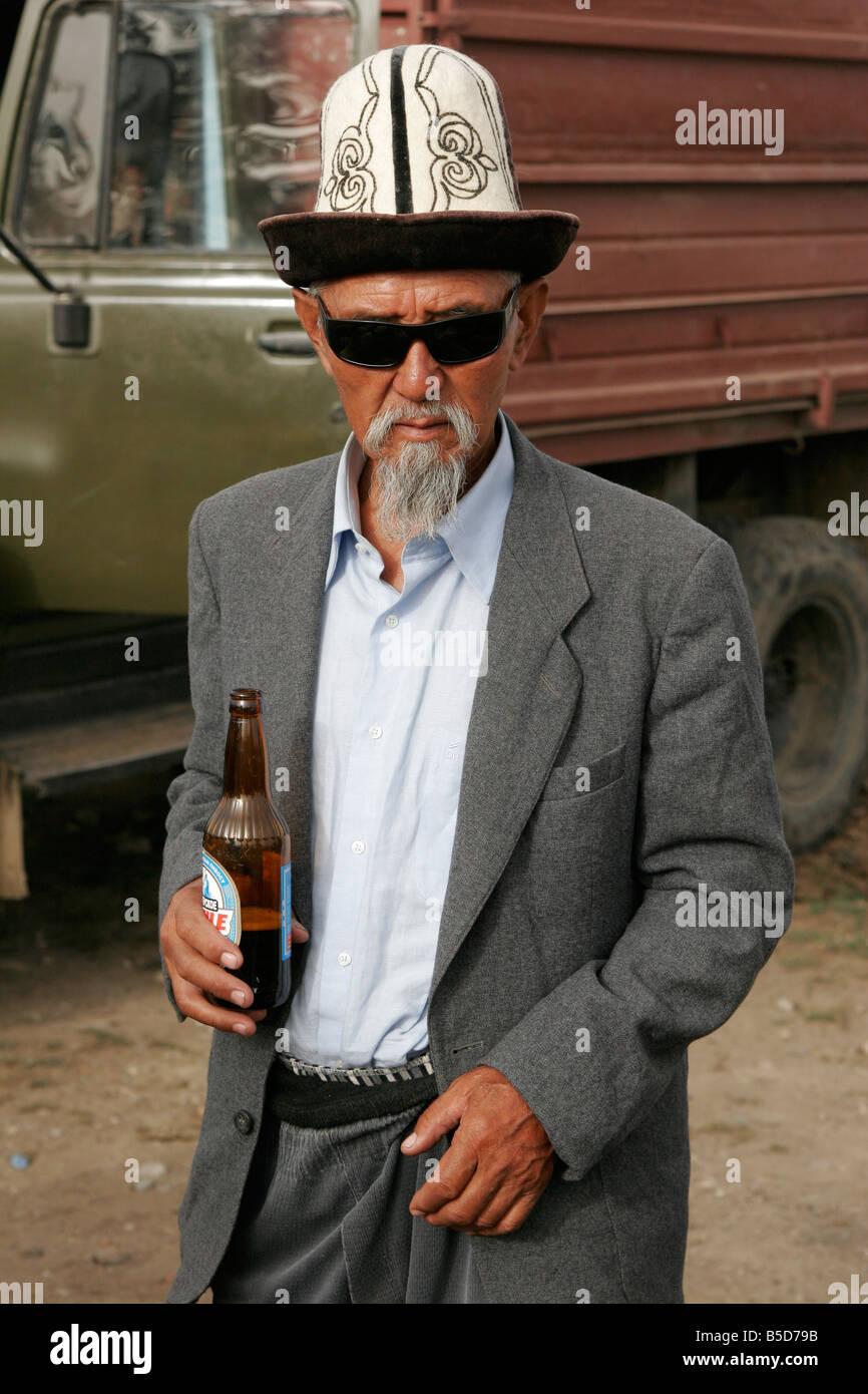 Il vecchio uomo del Kirghizistan indossando il tradizionale kalpak (HAT) in piedi con la bottiglia di birra, Kirghizistan, in Asia centrale Foto Stock