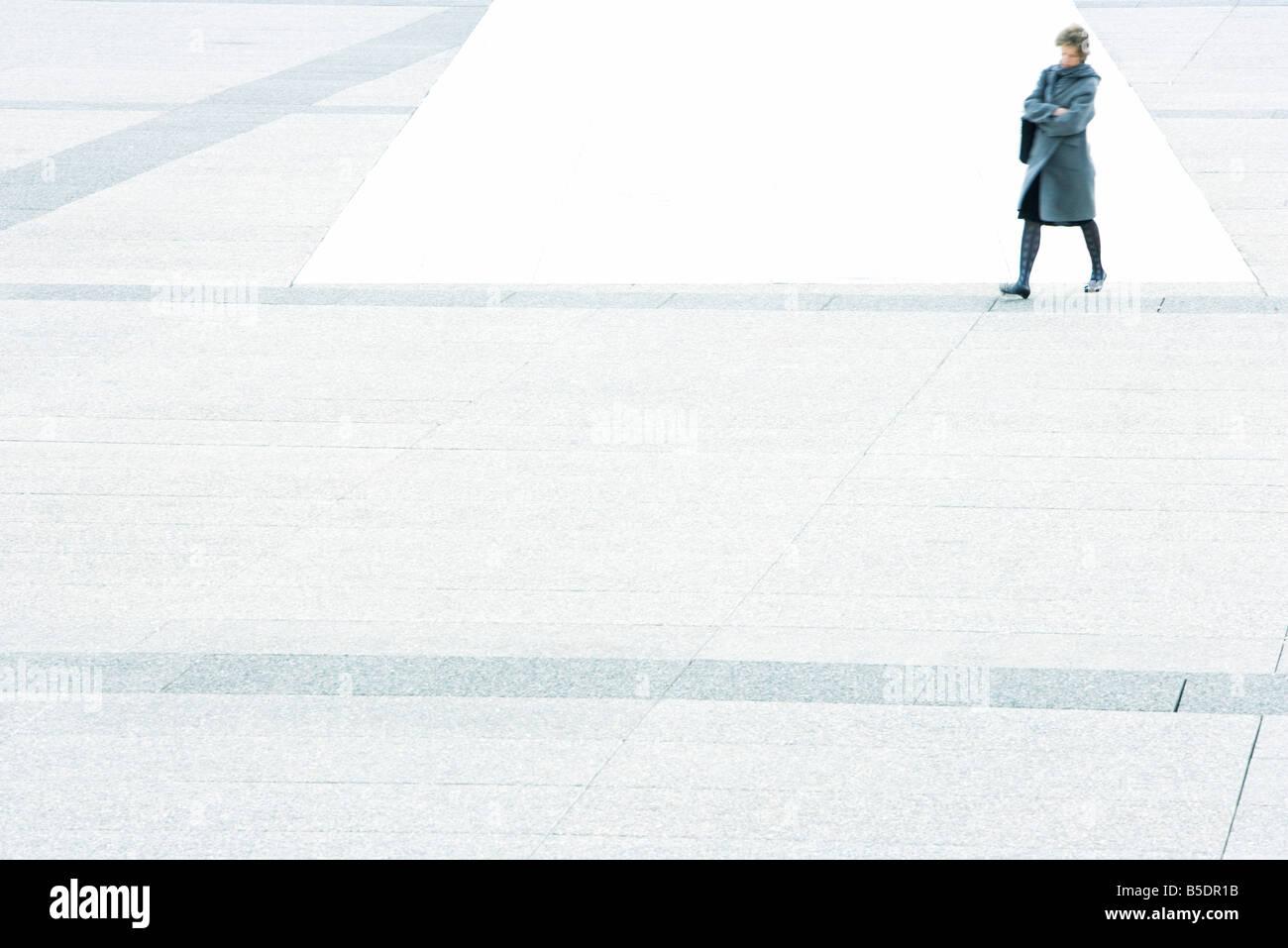 Donna con le braccia incrociate attraversando a piedi piazza della città Foto Stock
