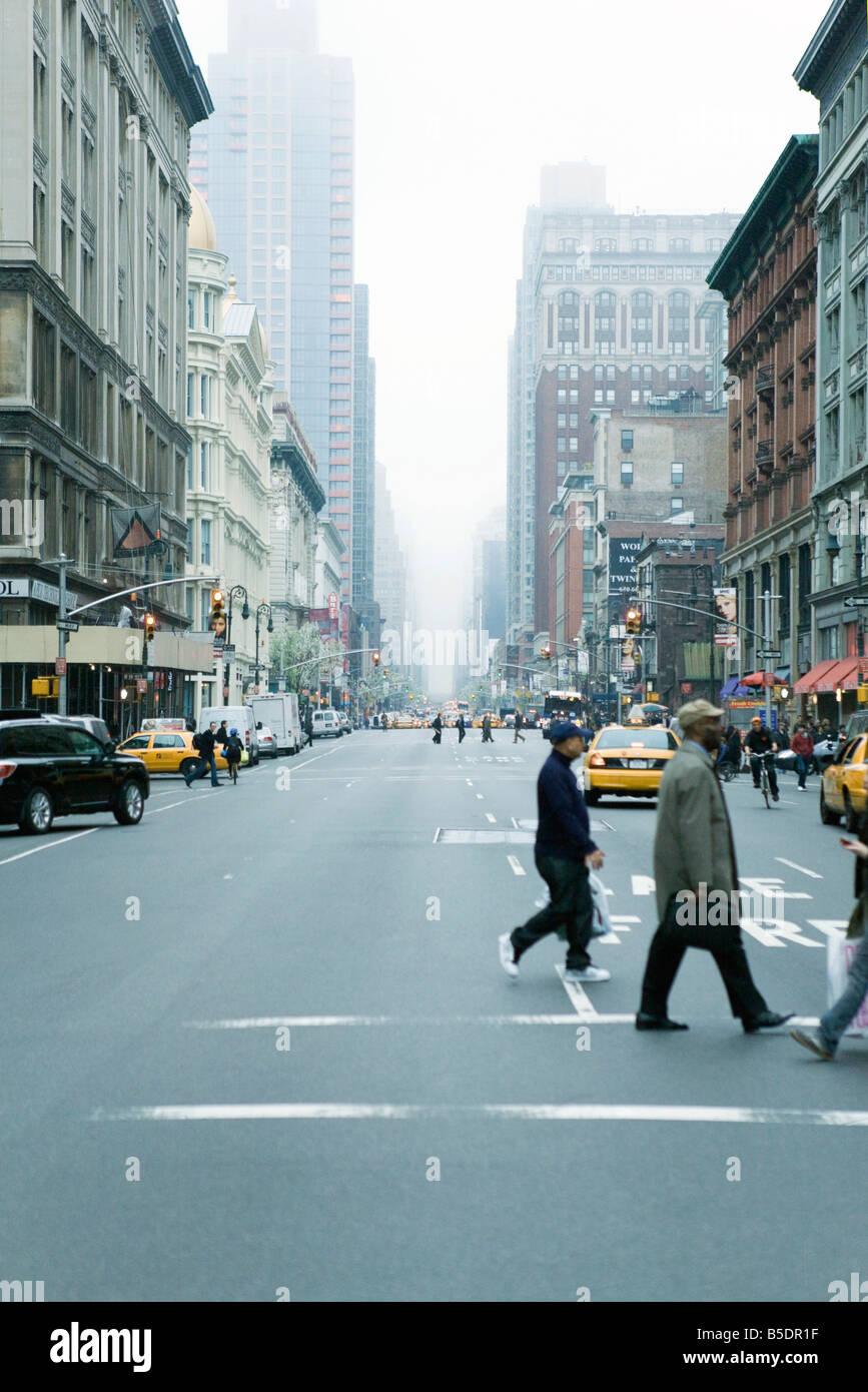 Pedoni che attraversano Via in crosswalk a W 19th Street e la 6th Avenue Chelsea, New York, rivolta ne Immagini Stock